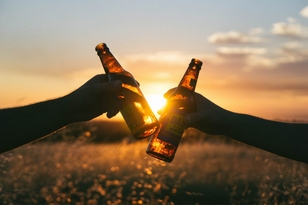 two people clinking beers