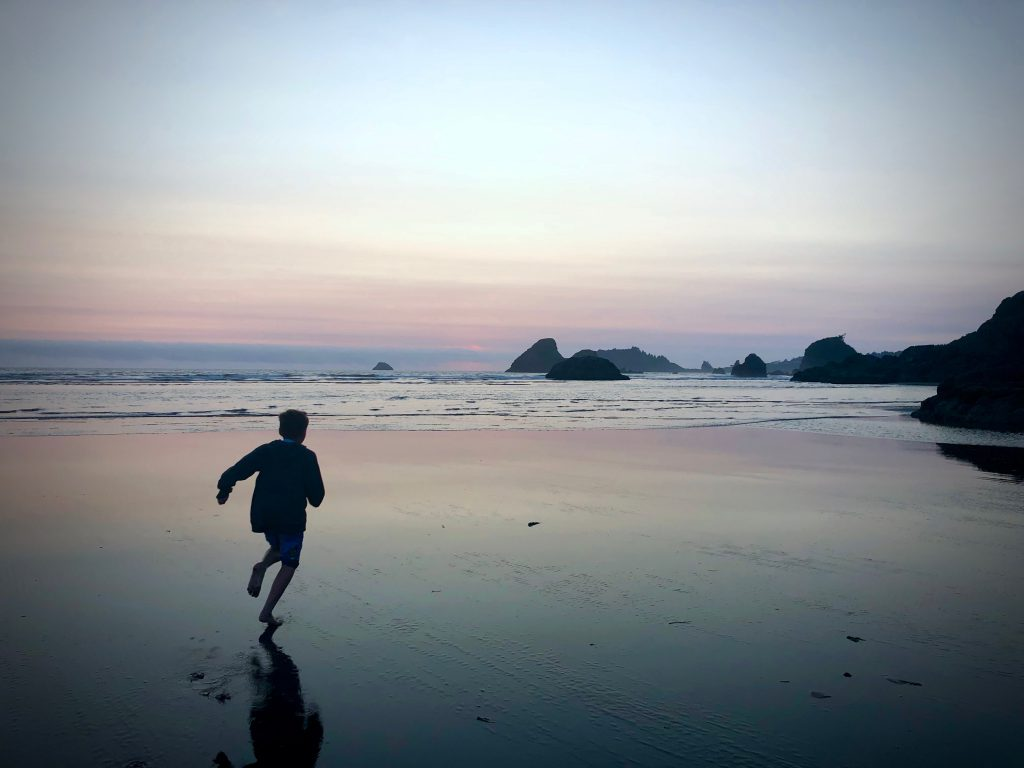 person running on the beach at sunset