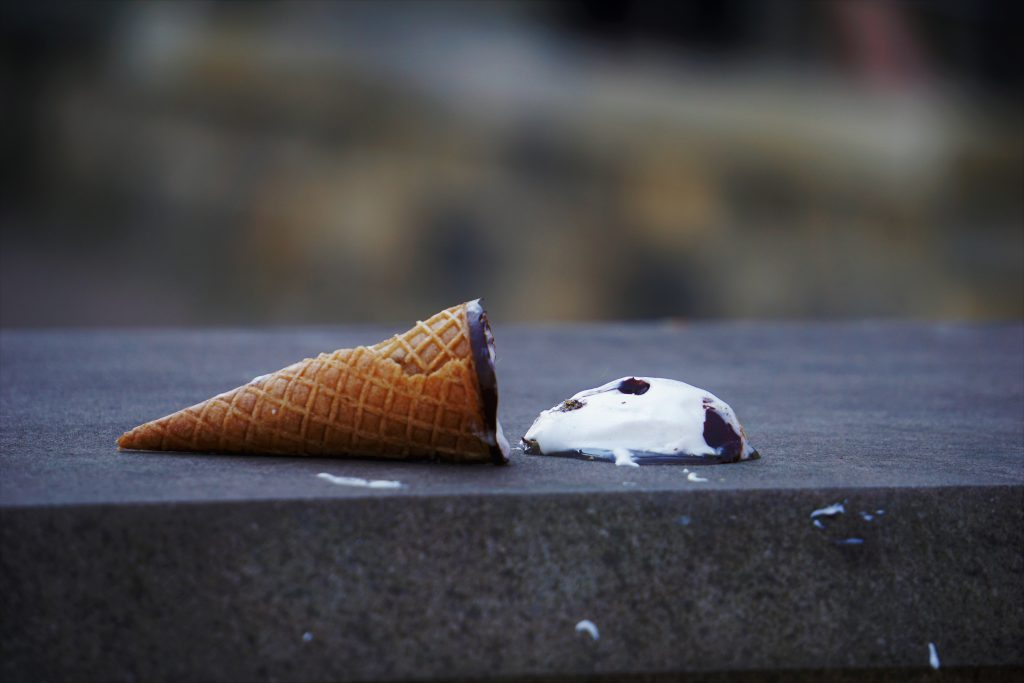 chocolate chip ice cream cone spilled and melting on the pavement